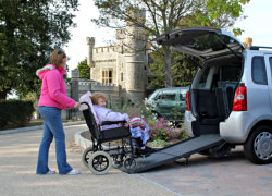 lady pushing elderly woman who's sitting on a wheelchair inside mobility transport